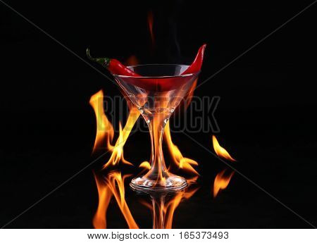 Flaming cocktail with peper over black background