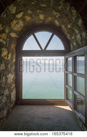 Old monastery window, overlooks the blue lake