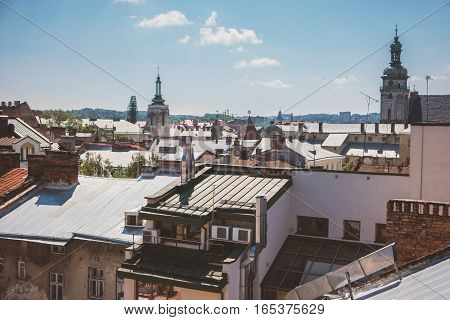 Town rooftops and sky. Church towers with crosses. Find the God's temple.