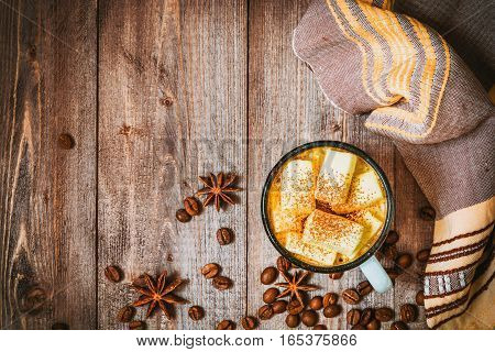 Cup of coffee with marshmallow on rustic wooden background. Top view.