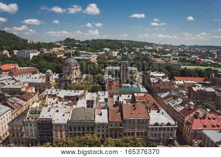 Town and sky at daytime. Green trees and buildings. Townscape in summer.