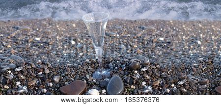 Wineglass, background of water flowing between rolling stones. sea pebbles on beach and sea wave - nature background.