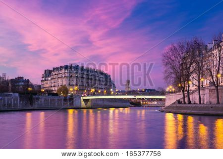 Picturesque grandiose sunset over Ile de la Cite, Seine River and Pont Saint-Louis, Saint-Jacques Tower in the background, Paris, France