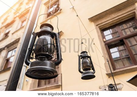 Black gas lamps. Lanterns near building. It's time for a journey.