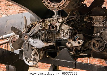 Parts of old engine. Steel wheels and fan. Start the heart of machine.