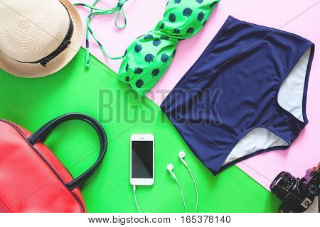 Flat lay set of summer items. Green color bikini with mobile phone and items for summer vacation on green and white background
