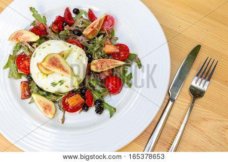Salad with marinated burrata figs cherry tomatoes and arugula