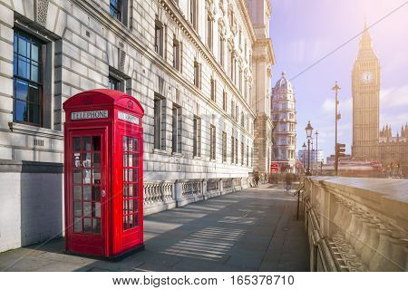 London England - Traditional red british telephone box with Big Ben and Double Decker bus at the background on a sunny afternoon