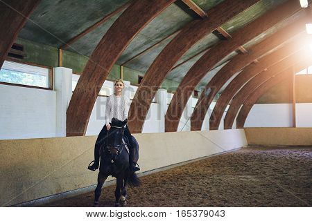 Female Riding Horse In Indoor Riding Hall