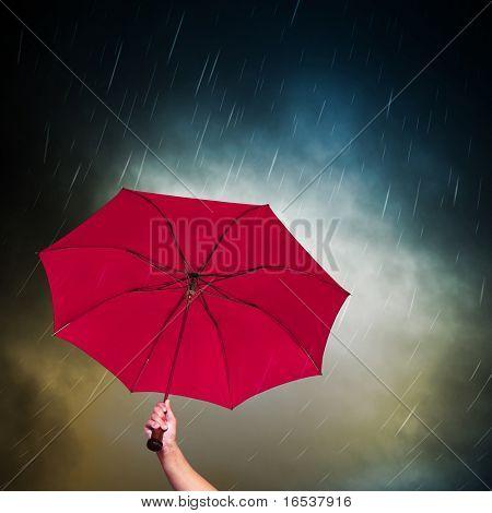 Opened pink umbrella under dark sky with falling rain