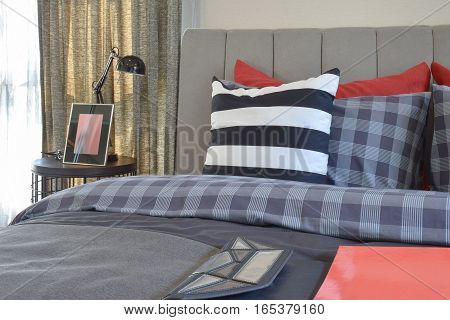 Modern Bedroom Interior With Striped Pillow On Bed And Bedside Table Lamp At Home
