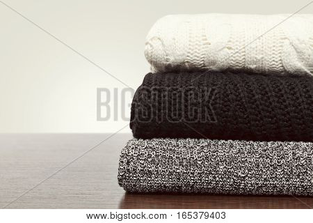 Stack of warm knitted sweaters. Empty space warm colors