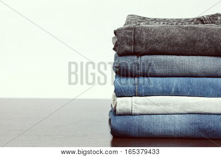Stack of jeans on wooden background with empty space vintage tone image