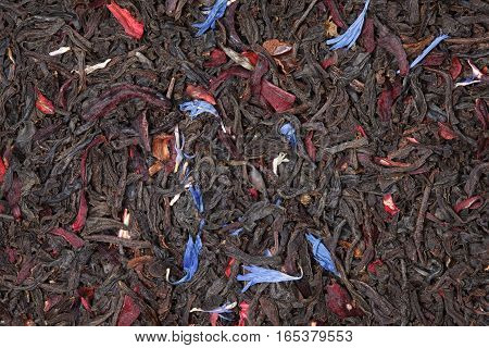 Black fruit tea background with flower petals