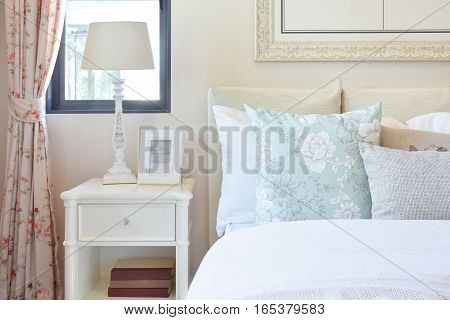 Vintage Bedroom Interior With Reading Lamp And Picture Frame On White Bedside Table
