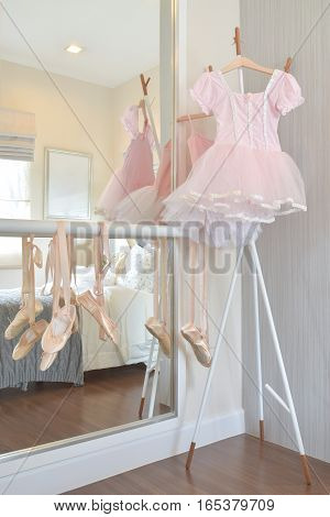 Girl's Pink Dress And Ballet Shoes Hang On Bar In Bedroom
