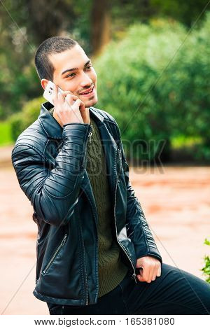 Happy young man with smartphone. Talking on the phone. A young and handsome boy is talking on the phone with someone. His mood is positive. Outdoors in a park.