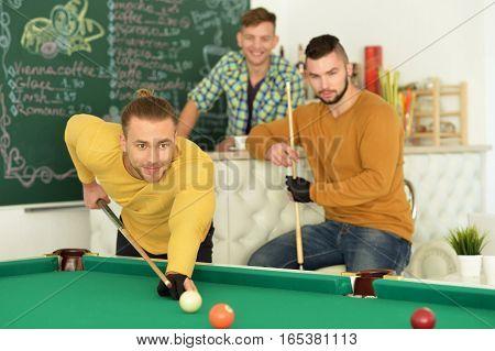 Portrait of three young handsome men play billiard