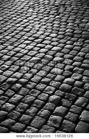 Background image of old cobblestone road backlit with low sunlight