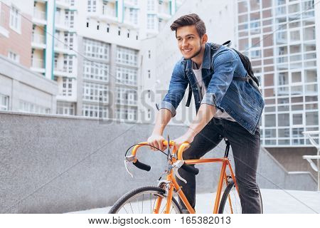 Man riding a bicycle outside. Attractive young boy in blue jeans jacket with white shirt underneath cycling with great joy to his friends. Urban background