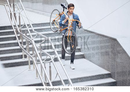 The guy in the blue jeans jacket carrying on his shoulder orange bike. A young handsome man with beard holding it on his right arm. He is going down stairs at work. Urban background