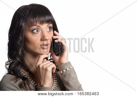 Portrait of young woman talking on the phone  isolated on white background