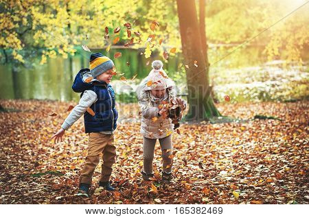 Two Children Playing With Leaves In Forest