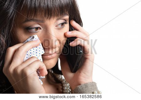 Portrait of young woman recieved bad news by the phone  isolated on white background