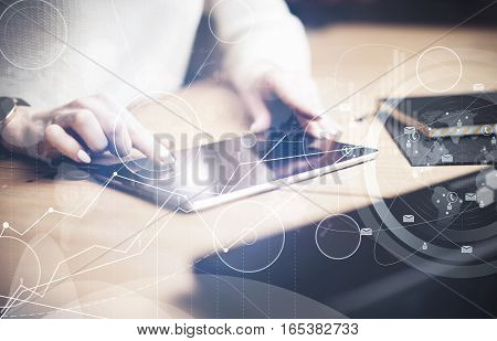 Concept of virtual interfaces, digital icons, online connections.Closeup view of female finger touching black screen digital tablet under the wooden table.Young business people using mobile devices