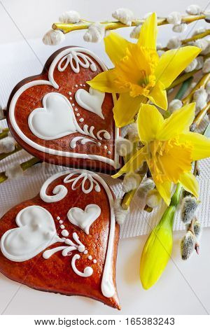Traditional Czech easter decoration - homemade gingerbread hearts cakes withpussycats and daffodils flowers on white background. Spring easter holiday arrangement.