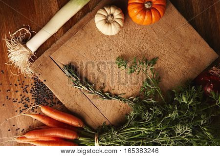 Black beluga lentils in a bowl, bunch of carrots, rosemary, leeks and miniature pumpkins lying around an old chopping board with deep cuts, top view presentation with space in center for your text