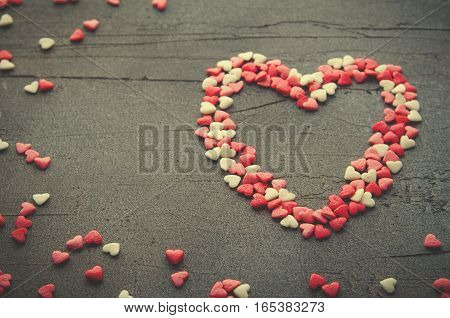 Heart made with small candy hearts, pink, red, whie colors, on dark background. Love, Valentine's day concept. Copy space, horizontal