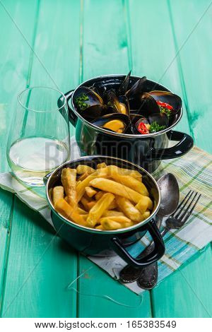 Mussels served with french fries and wine, copy space
