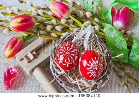 Traditional Czech easter decoration - regional wooden ratchet instrument with painted red eggs in wicker nest with pussycats and tulips flower. Spring easter holiday arrangement.