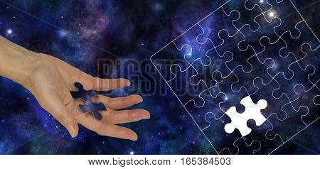 The Missing Piece of the Universe - Female hand holding a piece of jigsaw imprinted with the Universe on a Blue Universe Deep Space background and a jigsaw puzzle outline on right side