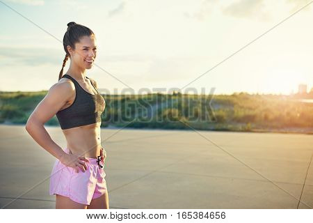 Fit beautiful young female athlete standing outside with hands on hips and big confident smile. Includes copy space.