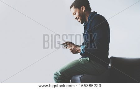 Attractive bearded African man using tablet while sitting on the sofa at his modern home office.Concept of young people working with mobile devices.Empty gray wall background