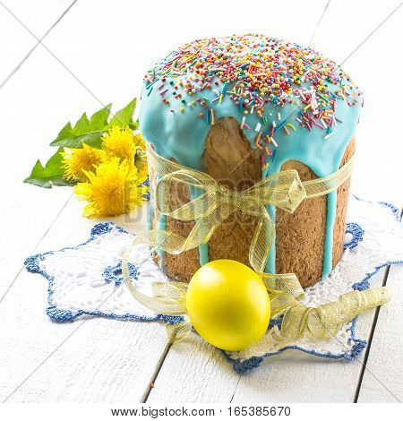 Traditional Easter treats: Easter cakes and colorful easter eggs on a white table. Square image