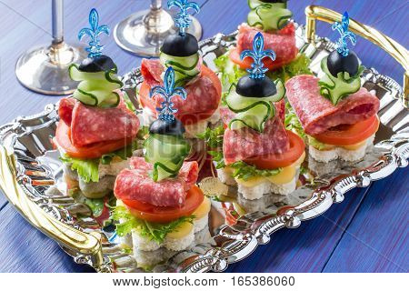 Colorful canape on skewers with vegetables and sausage on the tray. Tasty appetizer for a party or banquet. Selective focus
