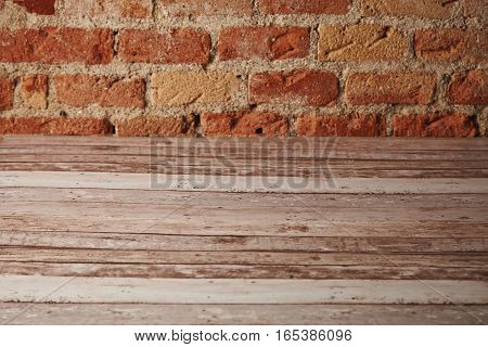 Empty rustic white worn wooden table with brick wall behind, background for still life and other compositions