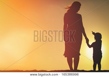 silhouette of mother and daughter holding hands at sunset sky