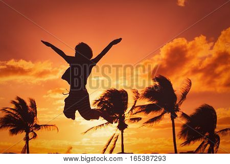 happy boy jumping at sunset beach, success and vacation love