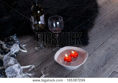 Two wine glasses heart shaped candles lingerie scattered in a party aftermath on silk and fur on floor horizontal view