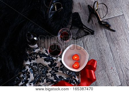 Two wine glasses heart shaped candles lingerie shoes scattered in a party aftermath on silk and fur on floor horizontal top view