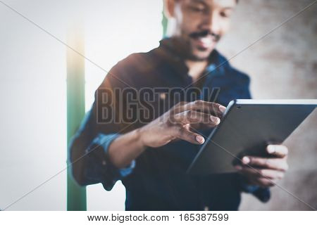 Attractive bearded African man using tablet while standing at his modern home office.Concept of young people enjoying mobile devices.Closeup with a focus male hand.Blurred background, flare effect