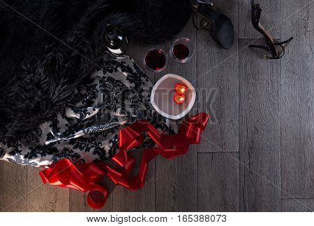 Two wine glasses heart shaped candles lingerie scattered in a party aftermath on silk and fur on floor horizontal top view with copy space