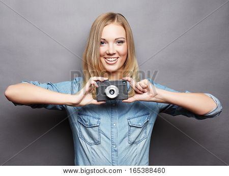 young happy blond woman  with vintage camera over grey background