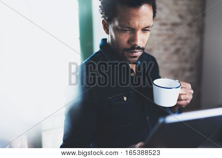 Closeup view of young bearded African man using tablet while holding white ceramic cup in hand at modern coworking office.Concept people working with mobile gadget.Blurred background.Color filter