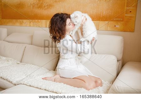 Cute Curly Girl In A White Silk Dressing Gown In The Early Morning Sitting On The Couch