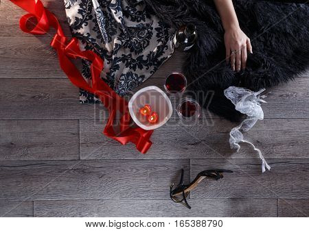 Two wine glasses heart shaped candles lingerie shoes scattered in a party aftermath on silk and fur on floor female hand rest on fur horizontal top view